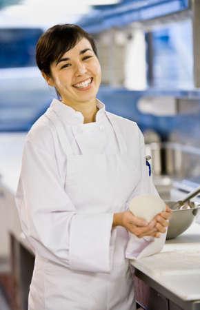 pacific islander ethnicity: Asian female chef holding dough