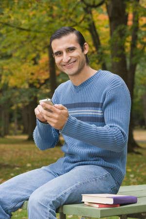 acknowledging: Hispanic man dialing cell phone LANG_EVOIMAGES
