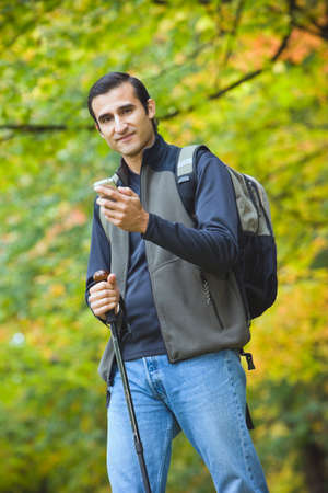 walking pole: Hispanic man holding walking pole and cell phone