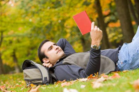 adventuresome: Hispanic man reading in grass LANG_EVOIMAGES