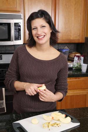 milepost: Pregnant Hispanic woman preparing food