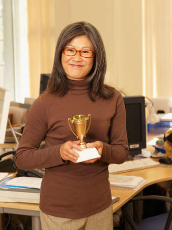 attired: Asian businesswoman holding trophy LANG_EVOIMAGES