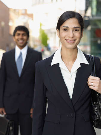 triumphing: Hispanic businesswoman in front of Indian businessman LANG_EVOIMAGES