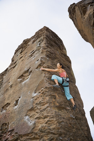 jeopardizing: Asian woman rock climbing LANG_EVOIMAGES