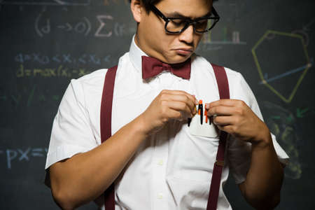 dubious: Nerdy Asian male student adjusting pencils in pocket