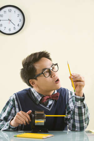 outmoded: Nerdy Asian man sharpening pencil LANG_EVOIMAGES