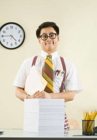 exactitude: Nerdy Asian man with stack of paperwork
