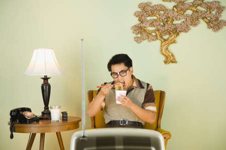 dubious: Nerdy Asian man eating in front of television LANG_EVOIMAGES