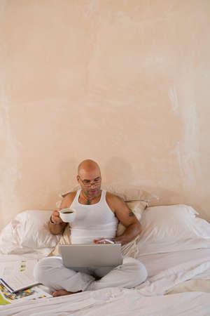 telecommuter: Hispanic man looking at laptop LANG_EVOIMAGES