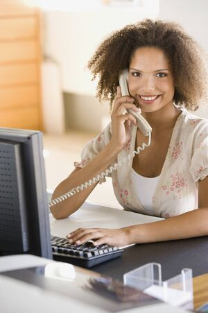 telecommuter: African businesswoman talking on telephone