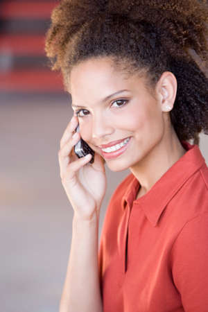 telecommuter: African woman talking on cell phone LANG_EVOIMAGES