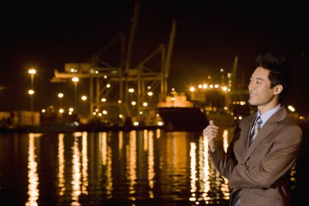 nite: Asian businessman next to water at night LANG_EVOIMAGES