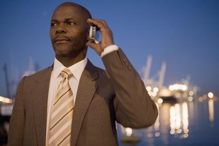 アフリカ系アメリカ人のビジネスマンが携帯電話で話しています。