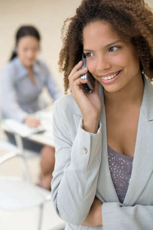 attired: African businesswoman talking on cell phone