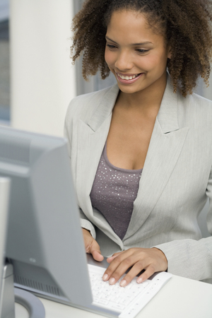 African businesswoman typing on computer Stock Photo
