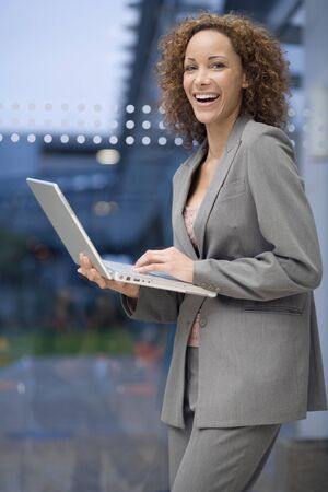 acknowledging: African businesswoman holding laptop
