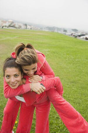 Middle Eastern woman giving sister piggy back ride Reklamní fotografie
