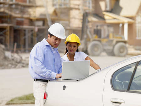 Asian couple with laptop at construction site