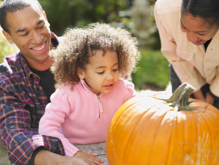 African family looking at pumpkin