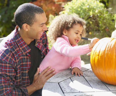 age 40 45 years: African father and daughter decorating pumpkin