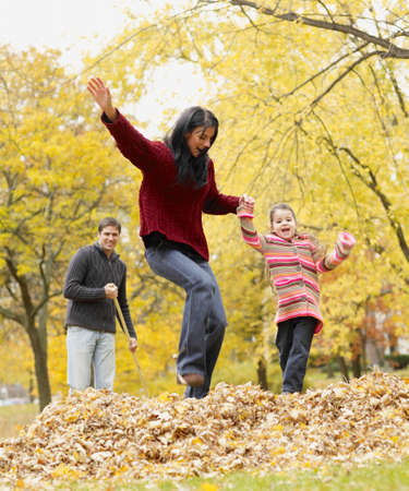 age 40 45 years: Multi-ethnic family playing in autumn leaves LANG_EVOIMAGES