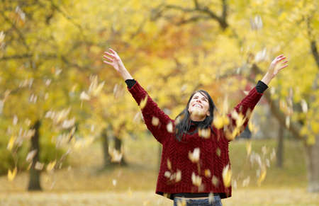 mischeif: Woman playing in autumn leaves