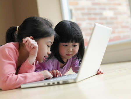 confiding: Asian sisters looking at laptop