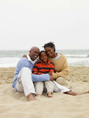 african american boy: African family sitting on beach LANG_EVOIMAGES