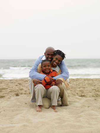 Afrikanische Familie sitzt am Strand