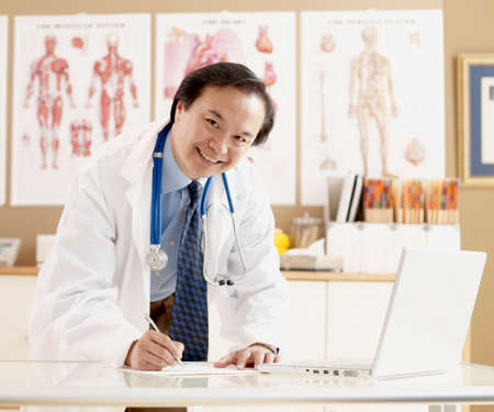 conferring: Asian male doctor writing at desk