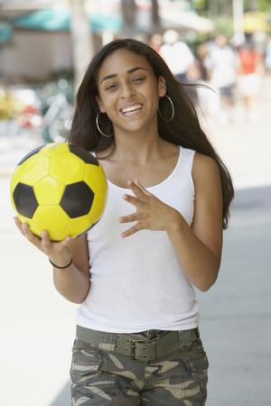teenaged girl: Mixed Race teenaged girl holding soccer ball
