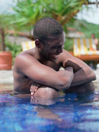 honeymooner: Hispanic man sitting in swimming pool