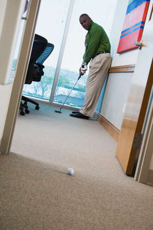 searcher: African businessman playing golf in office