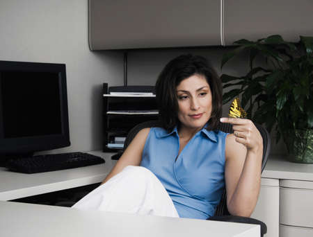 motioning: Hispanic businesswoman with butterfly on finger