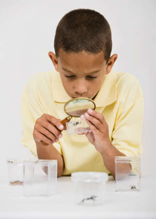 African boy looking at bug under magnifying glass