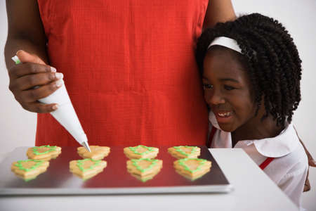 spectating: African girl watching mother decorate cookies