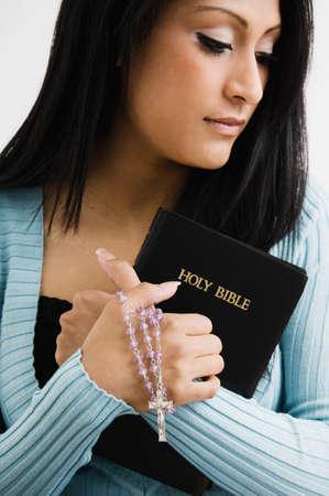 pleading: Hispanic woman holding bible