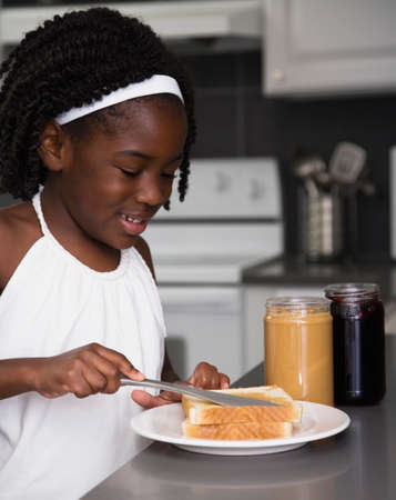 mischeif: African girl making sandwich LANG_EVOIMAGES