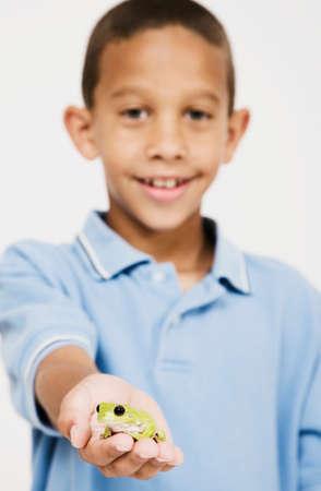 spectating: African boy holding frog LANG_EVOIMAGES