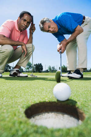 Multi-ethnic men looking at golf ball LANG_EVOIMAGES