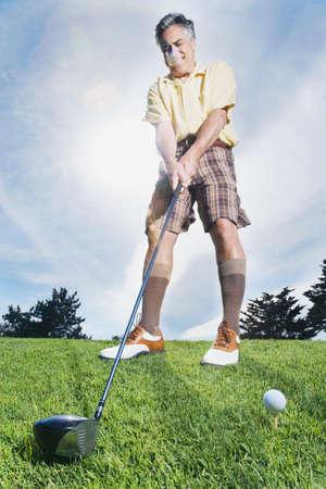 businessman pondering documents: Man swinging golf club