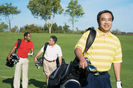 Multi-ethnic men on golf course LANG_EVOIMAGES
