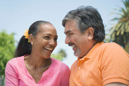 mischievious: Multi-ethnic couple smiling at each other