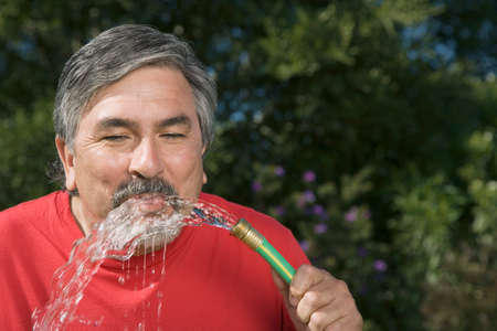 mischeif: Hispanic man drinking from hose