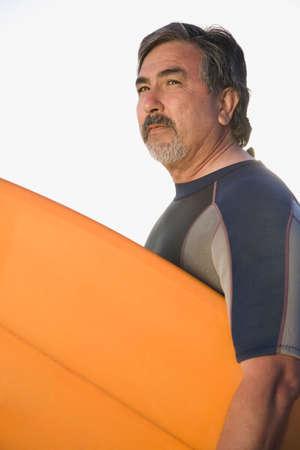 bathtowel: Hispanic man holding surfboard