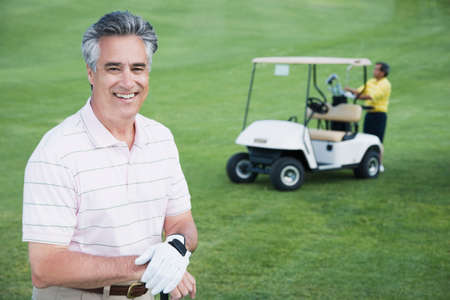 off course: Man in front of golf cart