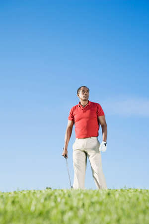 spectating: African man holding golf club