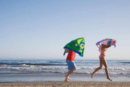 mischievious: Multi-ethnic couple running with beach towels LANG_EVOIMAGES