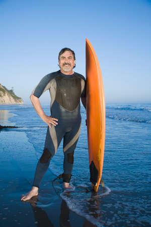 relishing: Hispanic man holding surfboard