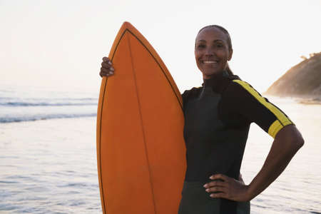 nite: Mixed Race woman holding surfboard LANG_EVOIMAGES